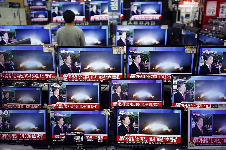 """A sales assistant in Seoul, South Korea, watching a news broadcast on North Korea's supposed hydrogen bomb test yesterday. A picture taken from North Korean TV showing a message from Mr Kim on starting the year with the """"thrilling sound of the first"""