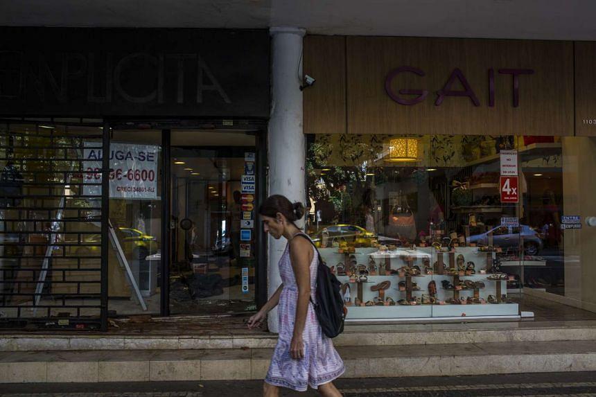 A pedestrian walks past an empty business space in Rio de Janeiro.