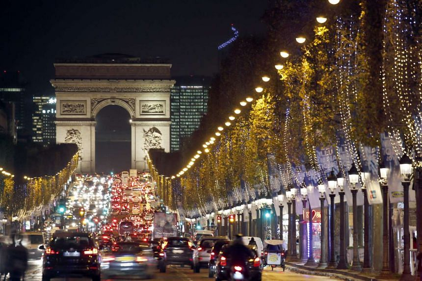 Christmas lights illuminate the Champs Elysees in Paris as rush hour traffic fills the famous avenue.