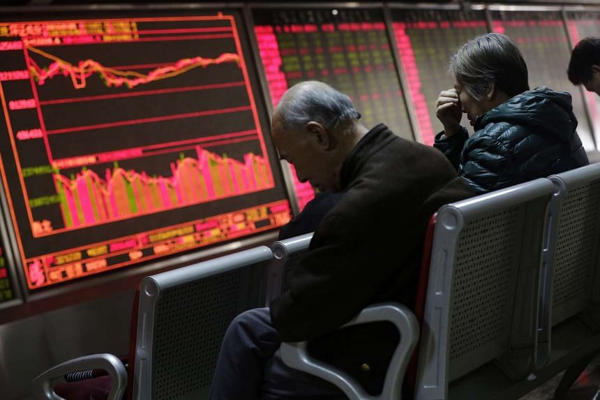 Investors looking at a screen showing stock movements at a brokerage house in Beijing on Jan 5.