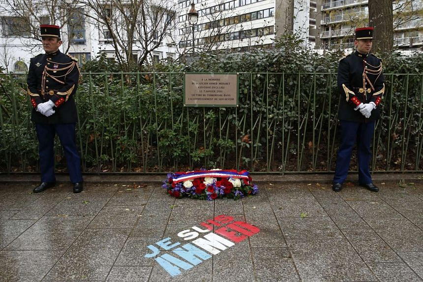A commemorative plaque is seen during a ceremony on Jan 6, 2016, at the site where policeman Ahmed Merabet was killed during the last year's January attack in Paris, France.