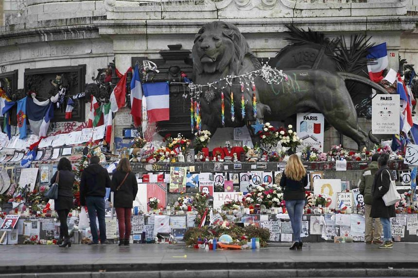 Flowers and messages to pay tribute to the victims of last year's attacks placed near the statue at the Place de la Republique in Paris, France, Jan 6, 2016.