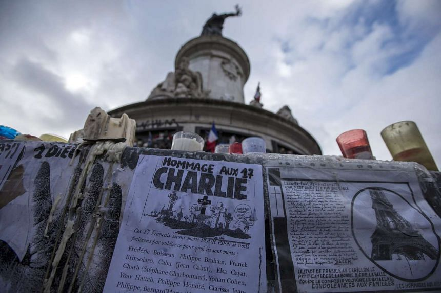 A poster paying tribute to the 17 victims of last year's January attacks in Paris adorns the monument on Place de la Republique in Paris, France, Jan 6 2016.