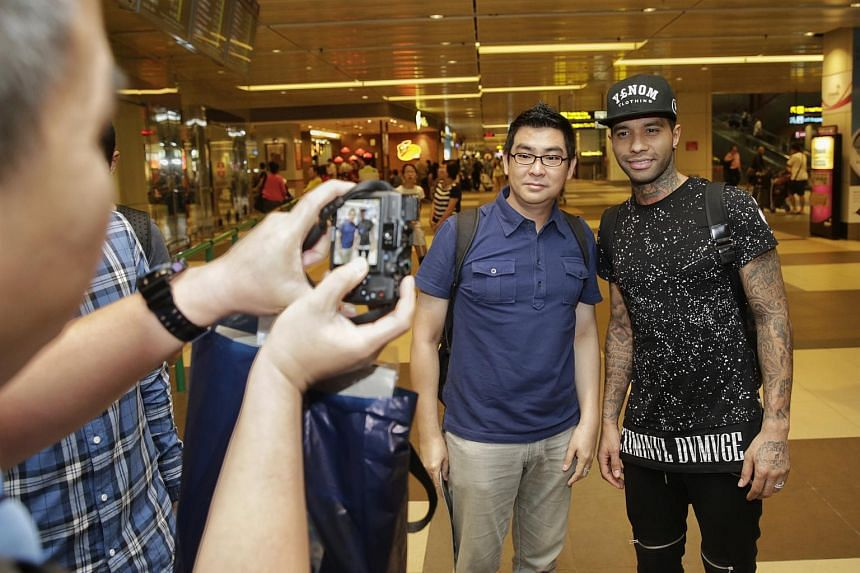 Jermaine Pennant posing for a picture with a fan in Singapore on Jan 7.