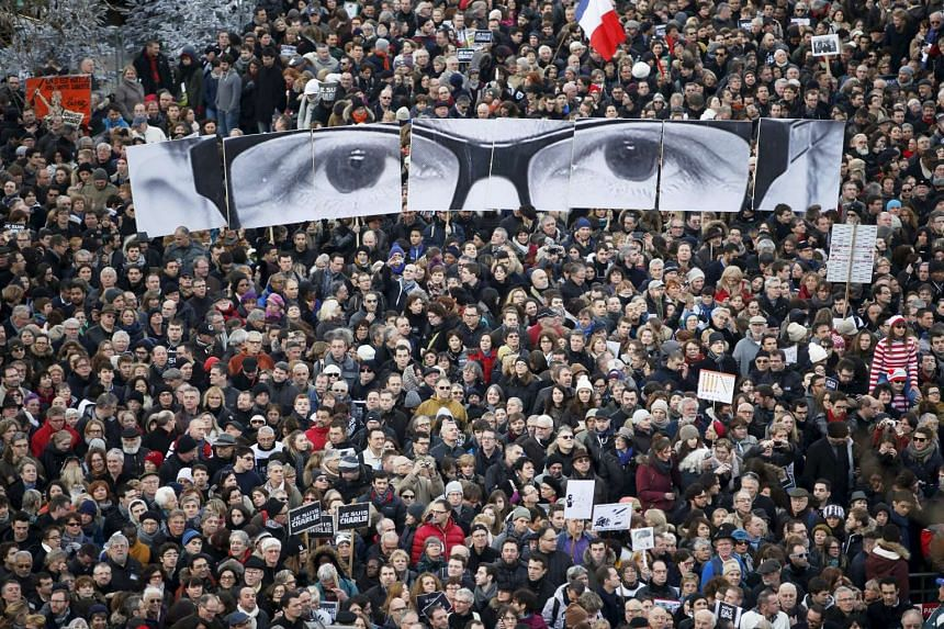 People hold panels to create an image depicting the eyes of late Charlie Hebdo editor Stephane Charbonnier as hundreds of thousands of French citizens take part in a solidarity march in Paris on Jan 11, 2015.