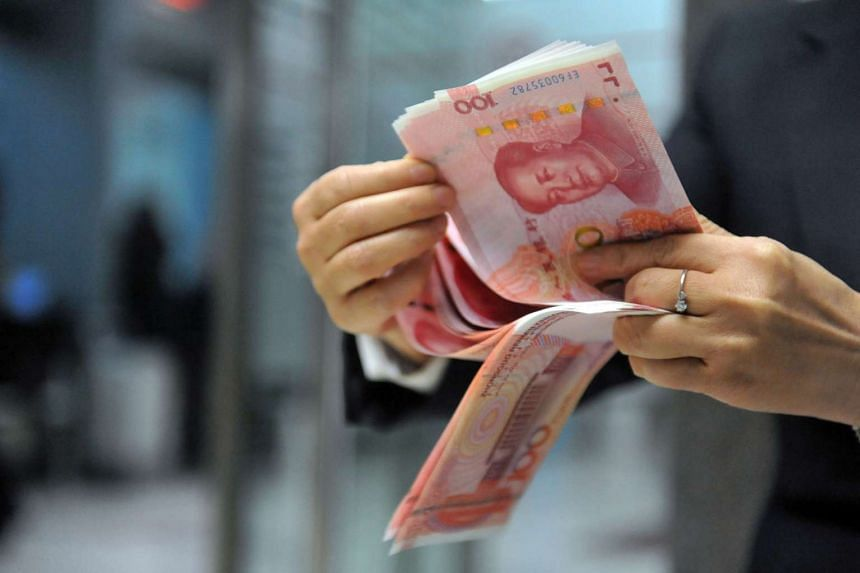An employee counting 100-yuan banknotes at a bank in Hangzhou on Dec 1, 2015.