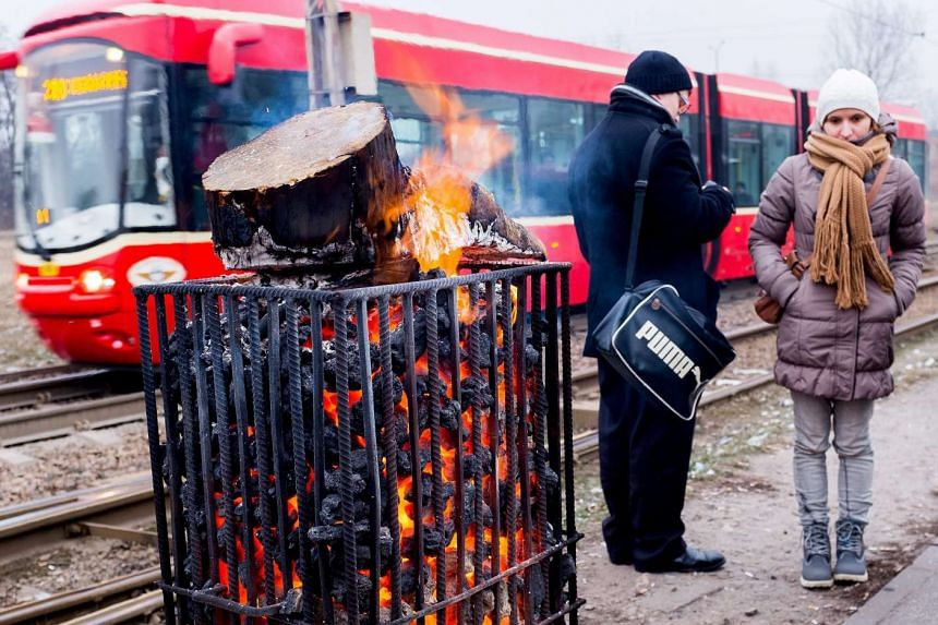 People warm themselves up by a fire in a bus station in Katowice, Poland on Jan 4, 2016.