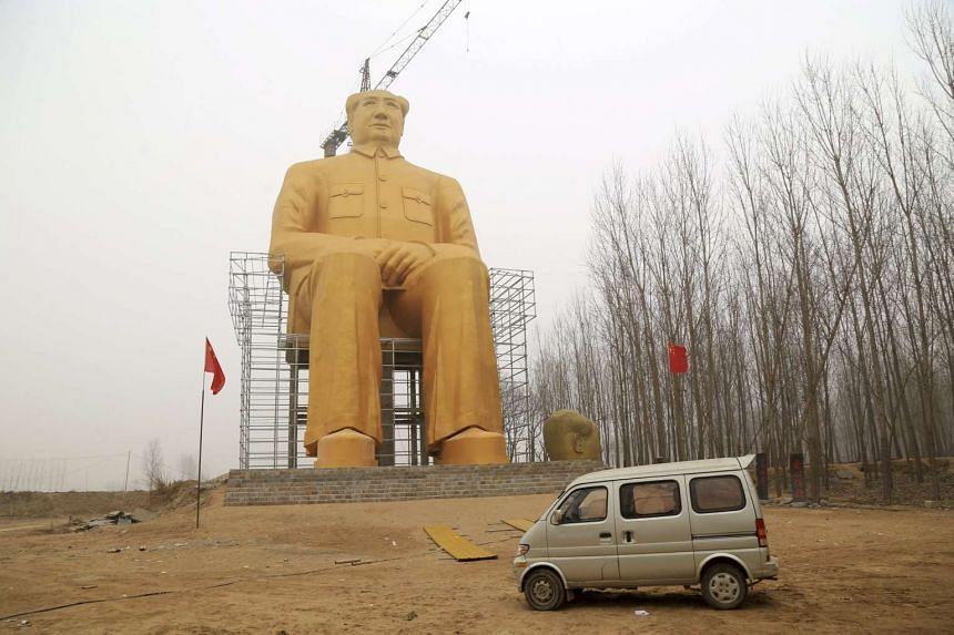 A car is seen parked in front of a giant statue of Chinese late chairman Mao Zedong in a village of Tongxu county, China.