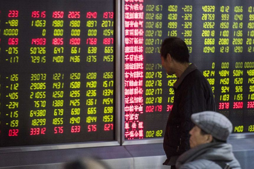 An man looking at screens showing stock market movements at a securities company in Beijing on Jan 5, 2016.