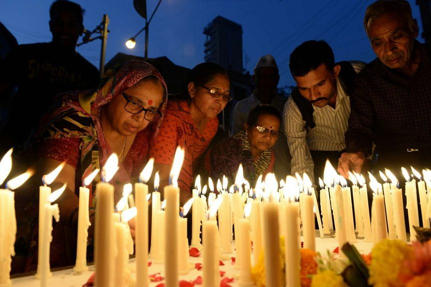 Mourners light candles during a vigil for Indian soldiers killed in an attack on an air force base in Mumbai.