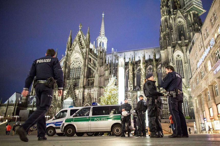 Police officers standing outside the main station next to Cologne cathedral, in Cologne, Germany.