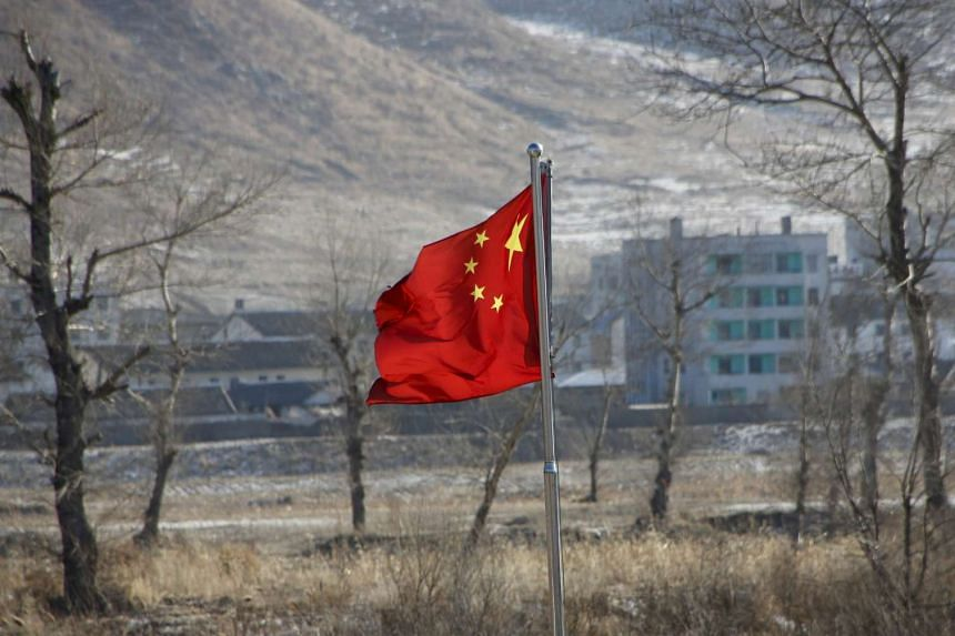 China's national flag flutters on the Chinese side of the banks of the Tumen river, as a North Korean village is seen behind, on Jan 7, 2016.