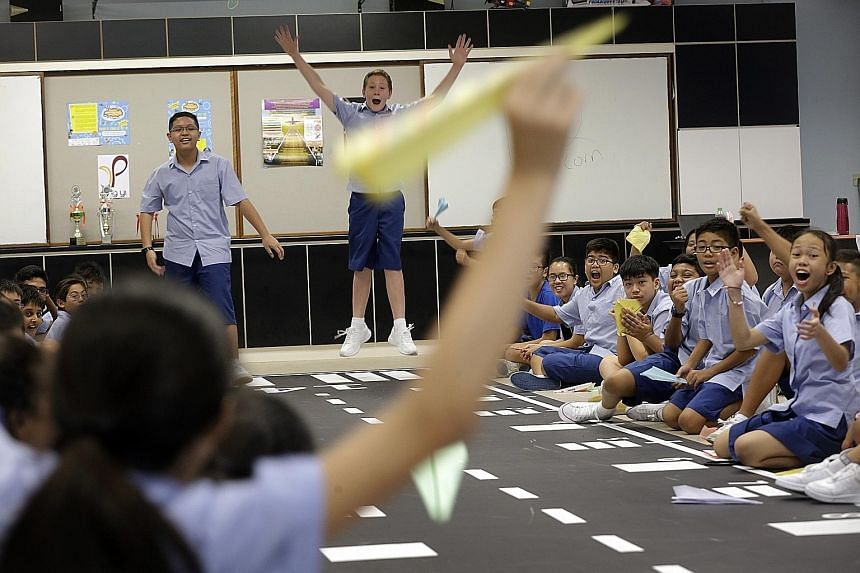 Sec 1 students of Ping Yi Secondary Haritz Mohd Hasri (left) and Noah John Mitchell taking part in a fun competition to see who can make a paper aeroplane that will fly the farthest. This activity reflects the merged Ping Yi Secondary's design and ae