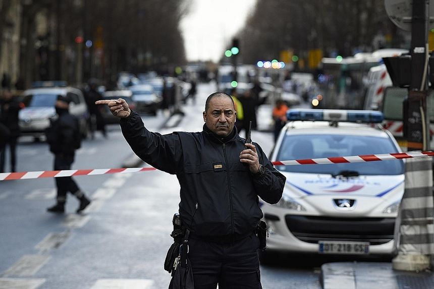 """A French policeman redirecting traffic at the Boulevard de Barbes in the north of Paris yesterday after a knife-wielding man attempted to attack a policeman at the reception of a police station in Paris """"before being hit by shots from the police""""."""