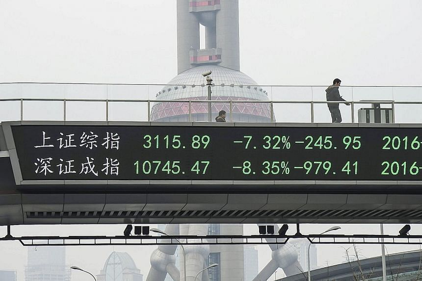 An electronic board showing the benchmark Shanghai and Shenzhen stock indexes on a pedestrian overpass in Shanghai, after the new circuit breaker mechanism suspended yesterday's stock trading.