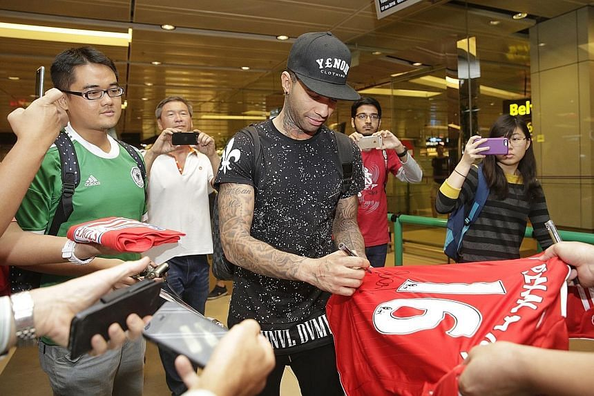 Former Arsenal and Liverpool winger Jermaine Pennant arriving at Changi Airport yesterday morning after a seven-hour flight from Dubai. He signed autographs and took photos with the handful of fans who greeted him.