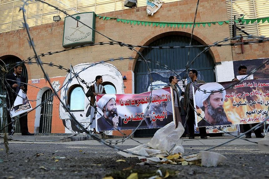 Supporters of the Iran-allied Houthi movement holding banners of prominent Shi'ite cleric Nimr al-Nimr, who was executed in Saudi Arabia last Saturday, during an anti-Saudi protest outside the Saudi Arabian Embassy in Sanaa, Yemen, yesterday.