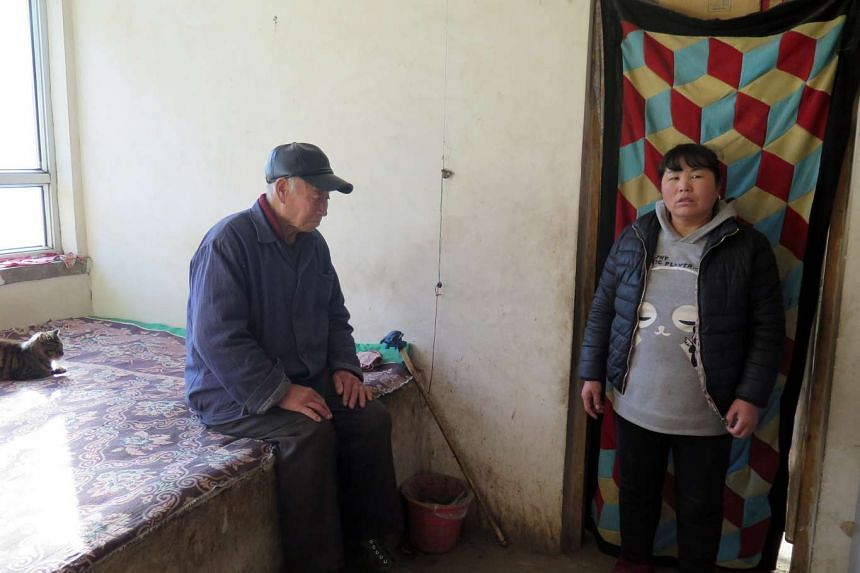 Madam Zhang Xiuzhen, 39, and her father-in-law Chang Yongbing, 85, in their sparsely furnished house in Aihetan Village, Hebei.