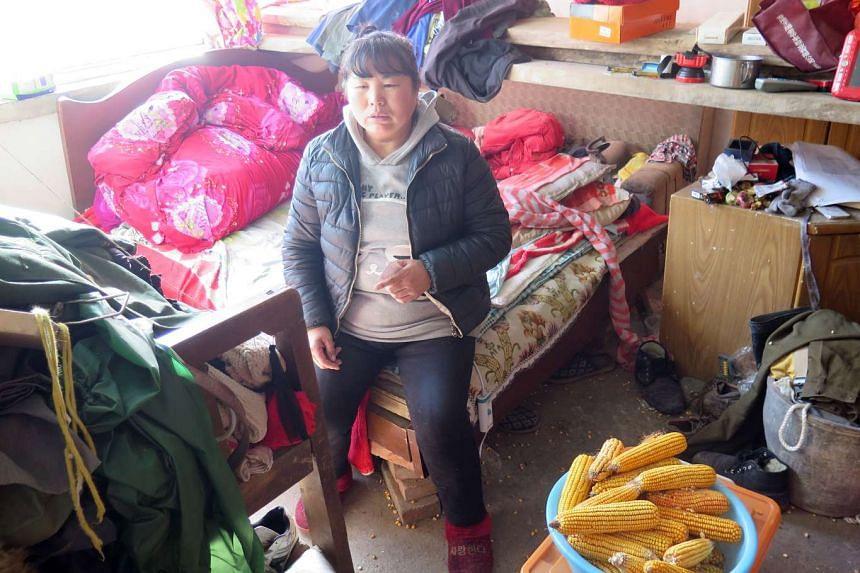 Madam Zhang Xiuzhen, 39, in her cluttered bedroom in Aihetan village in Hebei province.
