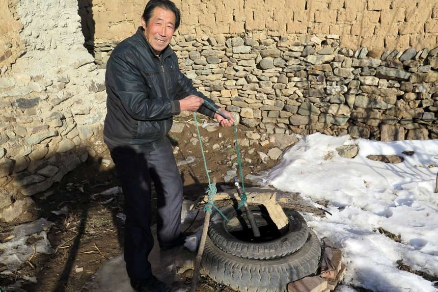 Aihetan villager Guo Zhanzhong, 67, drawing water from the village well.