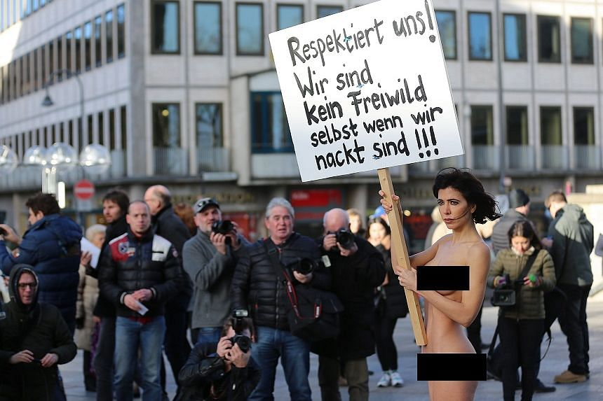 """A naked Moire holds a placard reading """"Respect us! We are not unprotected game even when we are naked!"""""""