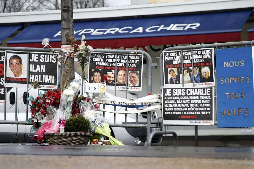 Flowers and messages in tribute to the victims of last year's January attacks are seen in front of the Hyper Cacher kosher supermarket.