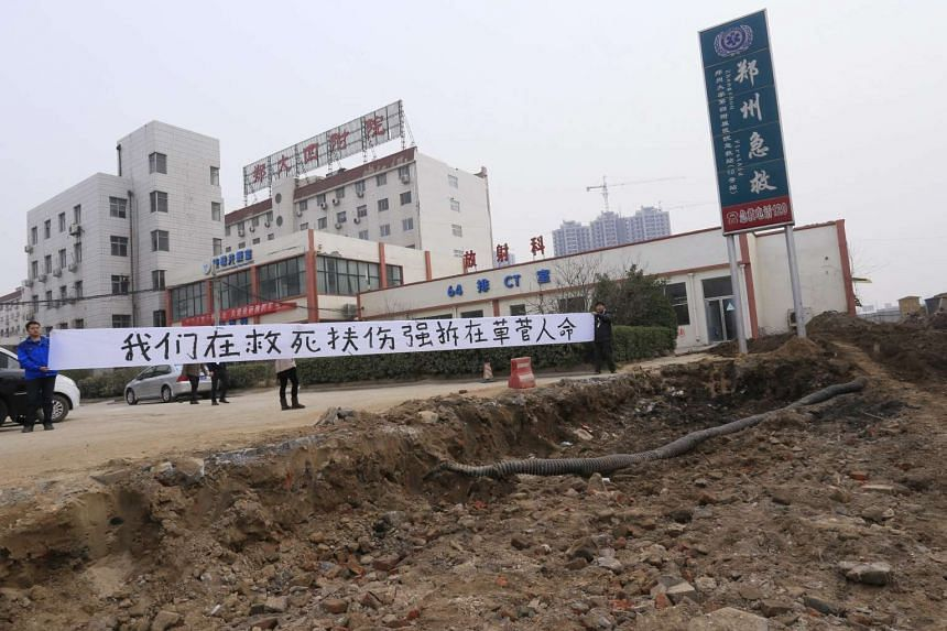 "Hospital workers putting up a banner which says: ""We are saving lives while the forced demolition is trashing lives."""