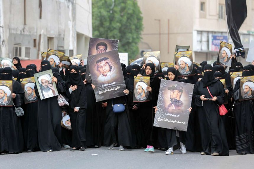 Saudi Shi'ite women holding placards bearing a portrait of prominent Shi'ite Muslim cleric Nimr al-Nimr during a protest on Jan 8, 2016.