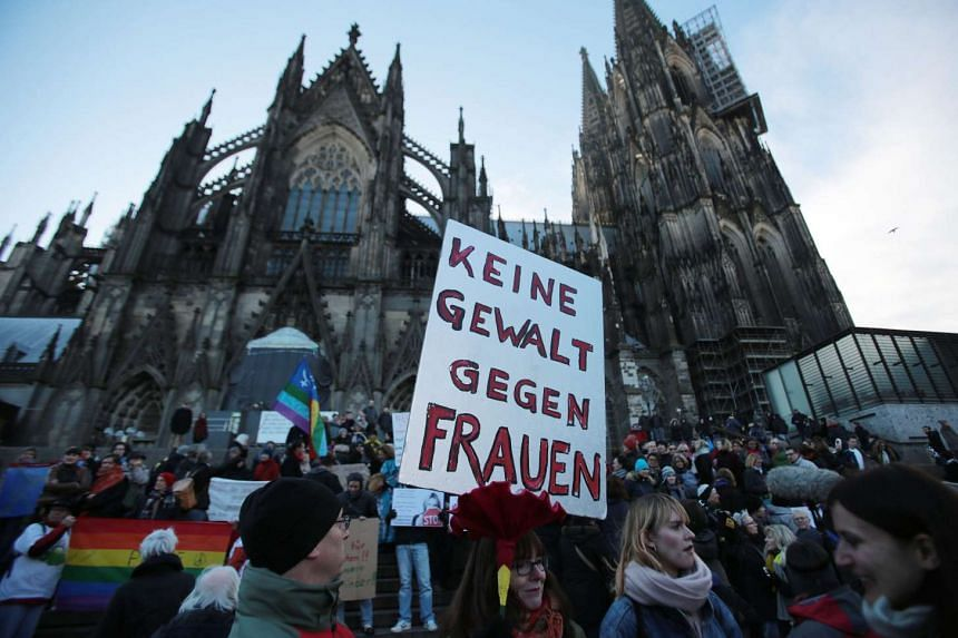"""A demonstrator holding a sign that reads """"No violence against women"""" during a demonstration in Cologne on Jan 9, 2016."""