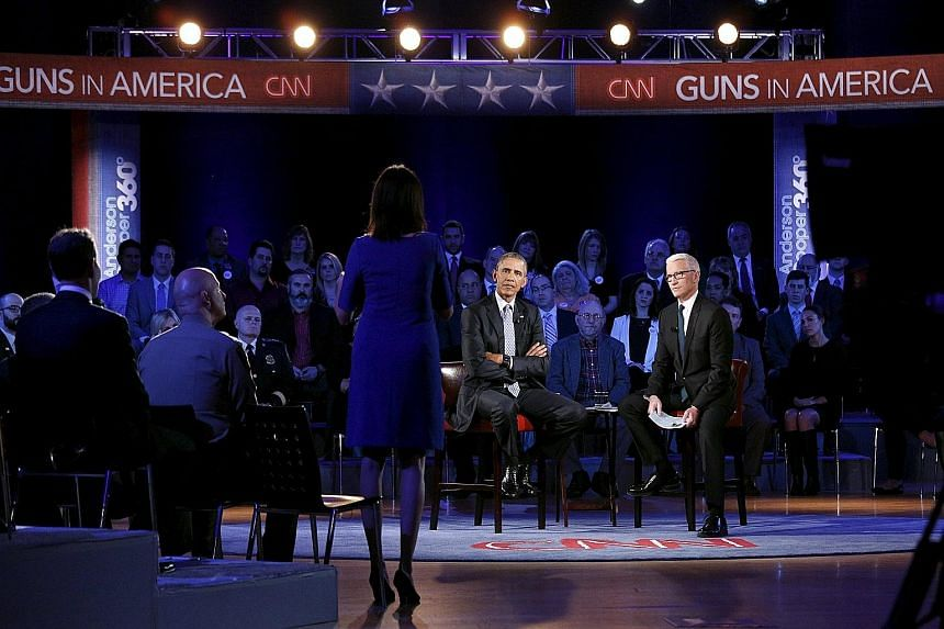 President Barack Obama (centre) listening to Mrs Taya Kyle, widow of Navy Seal Chris Kyle, during the town hall forum on gun control at George Mason University in Fairfax, Virginia. The event was hosted by CNN's Anderson Cooper (right).