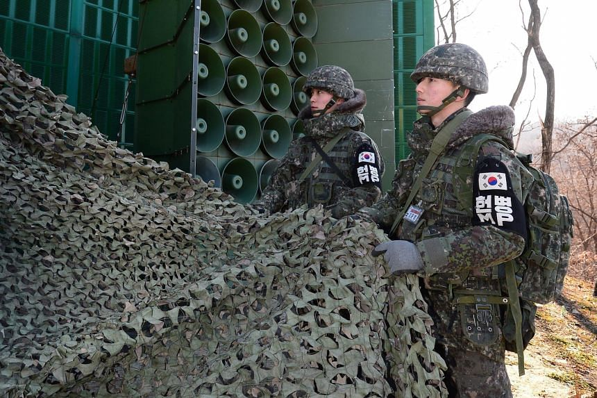 South Korean soldiers removing the camouflage as the loudspeakers were put to work again at the border yesterday. Seoul broadcast K-pop songs such as Bang, Bang, Bang by the group Big Bang and propaganda messages aimed at the North in retaliation aga