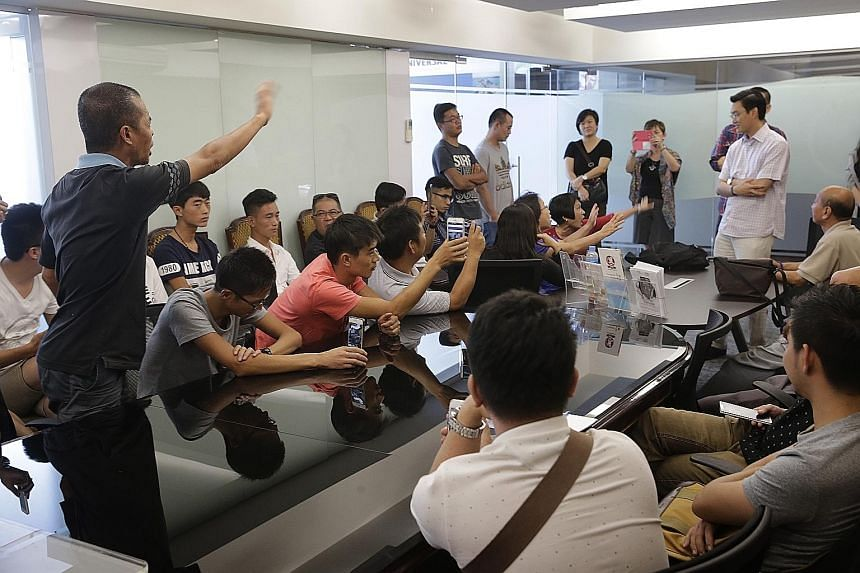 Former employees of Singapore River Explorer demanding compensation yesterday from Mr Nelson Goh (standing, in white), a director of Leisure Empire which co-owned the company with Global Yellow Pages. They were laid off when it ceased operations on D