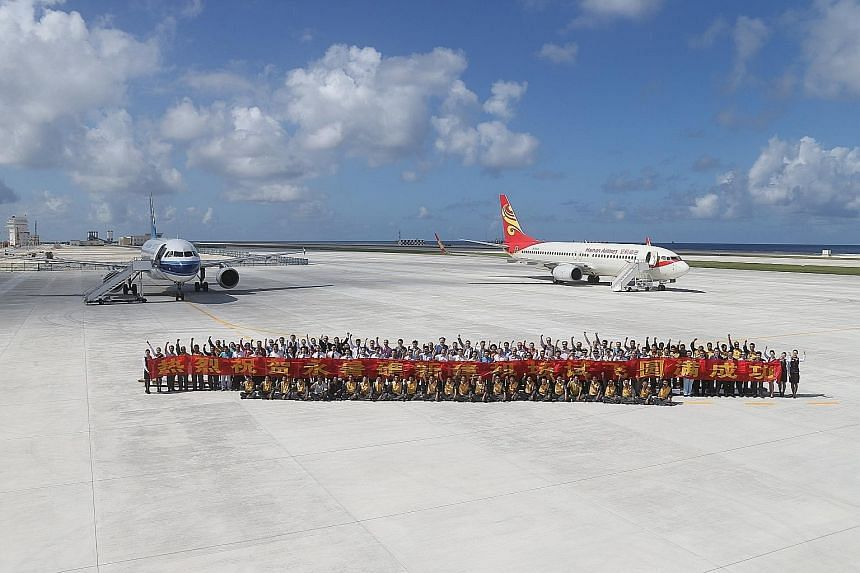 (Left) The two Chinese test flights that landed on Fiery Cross Reef, which China calls Yongshu Jiao, in the South China Sea on Wednesday. (Above) Hanoi maintains that the newly built 3,000m-long airstrip on the reef, which allows for bigger and heavi