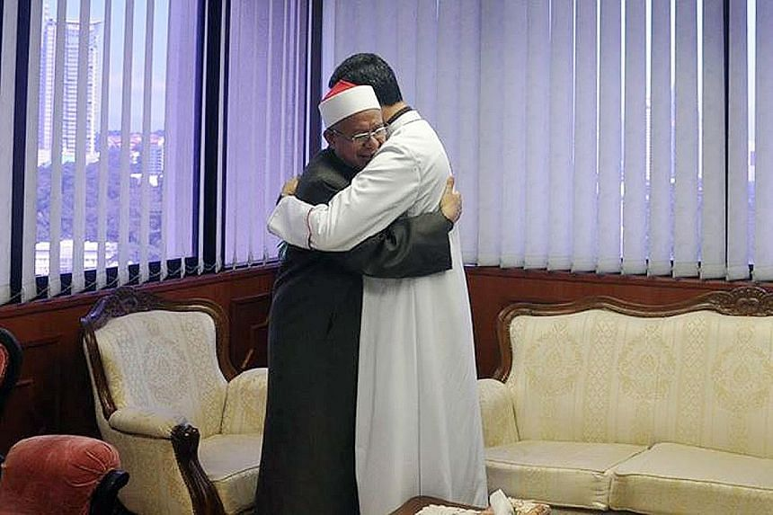 Mufti Zulkifli (in black) embracing Archbishop Leow in the ground-breaking meeting on Thursday. The two leaders shared views on the importance of being tolerant towards each other's religion.