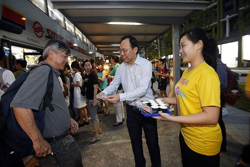 Holland-Bukit Timah GRC MP and Zhenghua grassroots adviser Liang Eng Hwa (centre), as well as grassroots leaders from the Zhenghua division, giving out cookies and around 300 cups of coffee and Milo on Thursday to perk up morning commuters in the fir