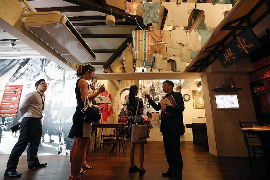 Mr Razeen Chan (extreme right), director for Research, Training and Consultancy at Singapore History Consultants, showing members of the media the gallery illustrating Chinatown in the 1960s.