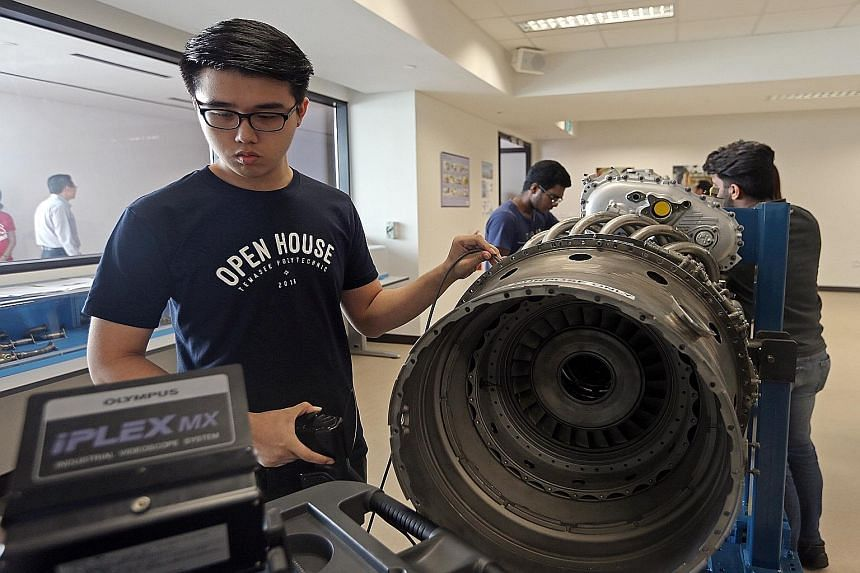 Aerospace Engineering student Poh Kiat Wei, 19, at the Engine Training Workshop during the opening of Temasek Poly's aviation academy yesterday. The academy has facilities that include an aircraft-access training hangar, a wind tunnel and flight simu