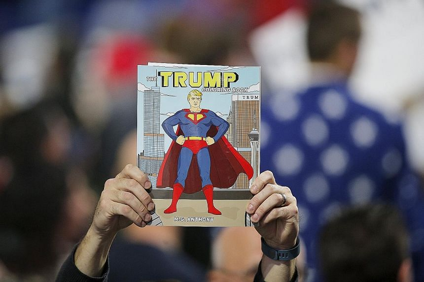 A supporter holding up The Trump Coloring Book at a campaign rally for US Republican presidential candidate Donald Trump. Mr Trump, 69, has never hesitated to offer himself as the incarnation of the American Dream.