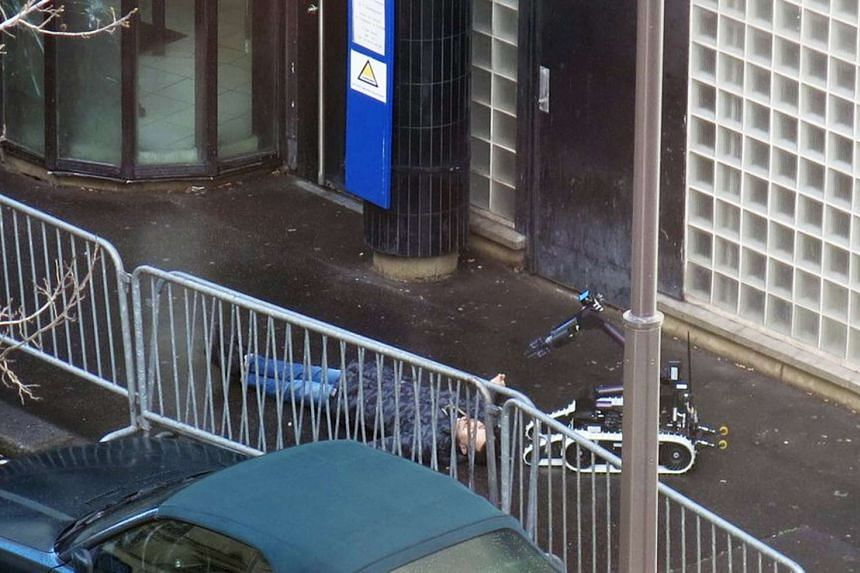 French police use a bomb disposal robot to inspect the body of the man said to be Tarek Belgacem.
