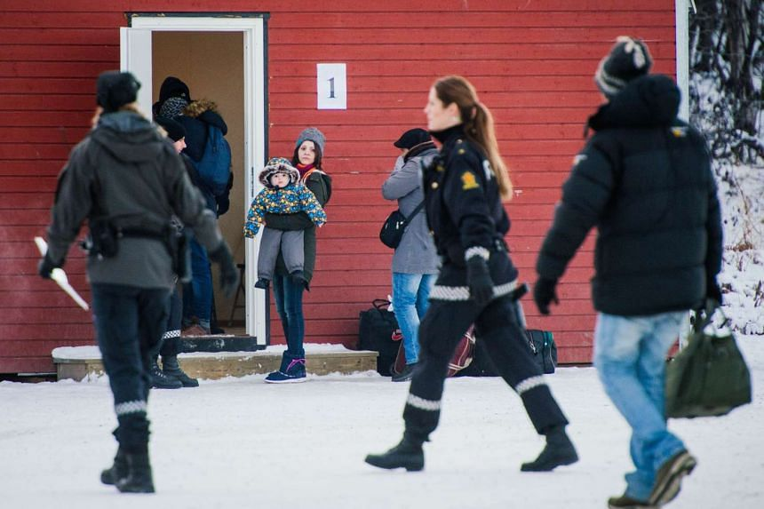 Refugees are welcomed upon arrival at the Norwegian border after crossing from Russia.