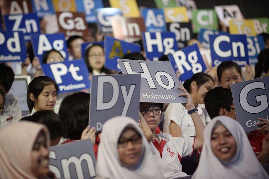 Students holding up cards with symbols from the periodic table during a lecture at the Singapore Science Centre on July 30, 2013.