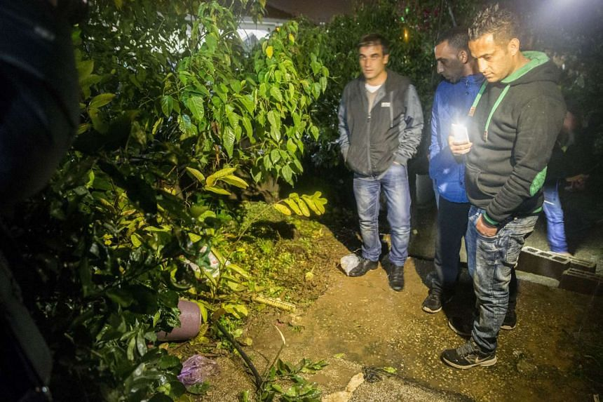 People gather at the site where Israeli special forces shot a suspected Arab Israeli gunman.