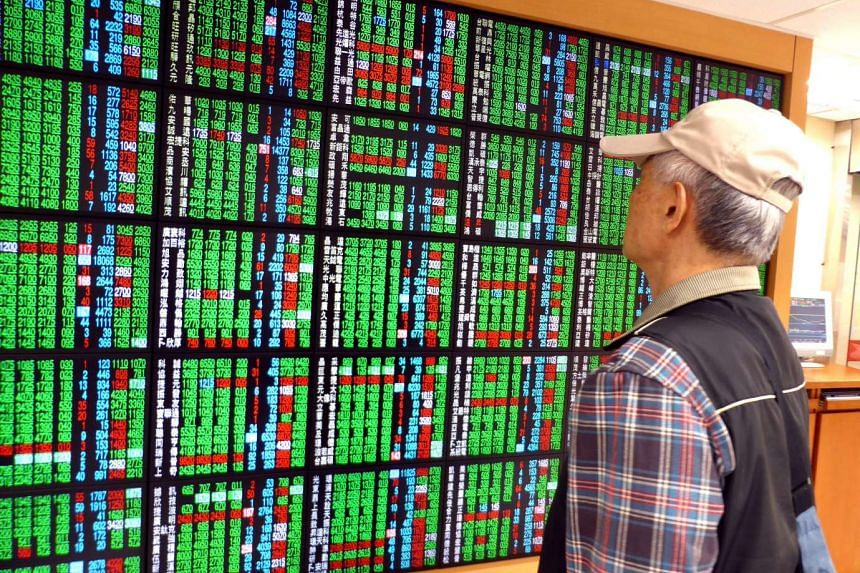 A man watches an electronic display board at a brokerage in Taipei.