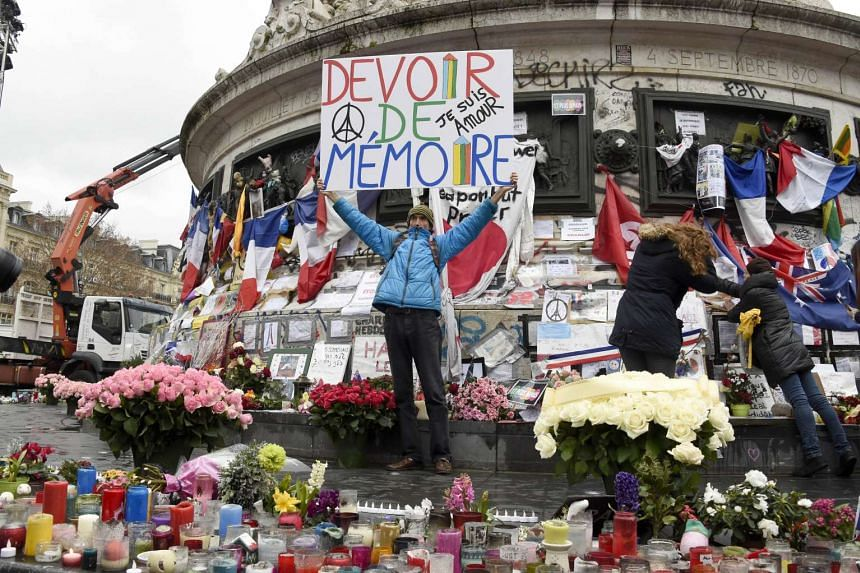 """Jean-Baptiste Redde holds-up a banner that reads, """"We must remember"""" following a remembrance rally at Place de la Republique on Jan 10, 2016."""