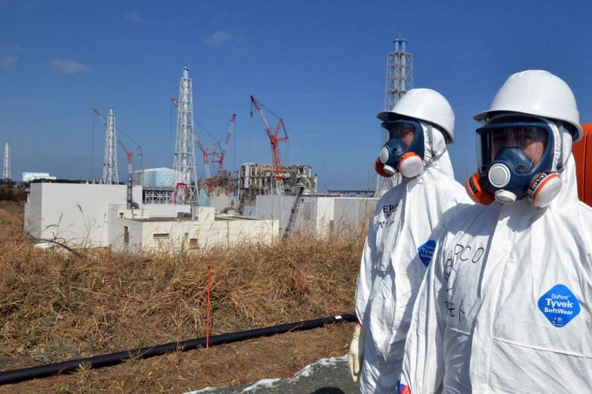 Workers standing outside the Fukushima Dai-ichi nuclear power plant in Okuma town on Feb 28, 2012.