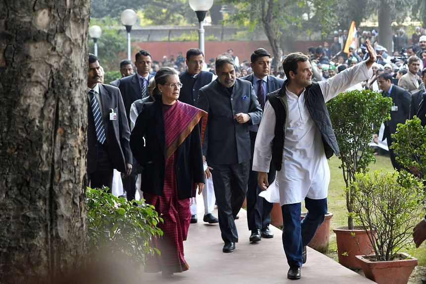 Rahul Gandhi (right) waves as he walks with his mother and party President Sonia Gandhi towards a media briefing on Dec 19, 2015.