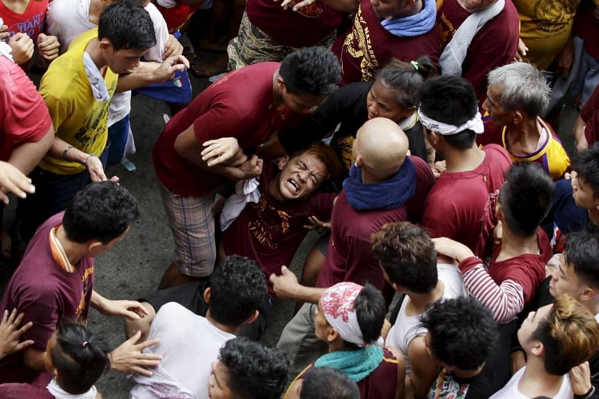 Devotees help an injured man during the annual procession of the Black Nazarene in Manila.