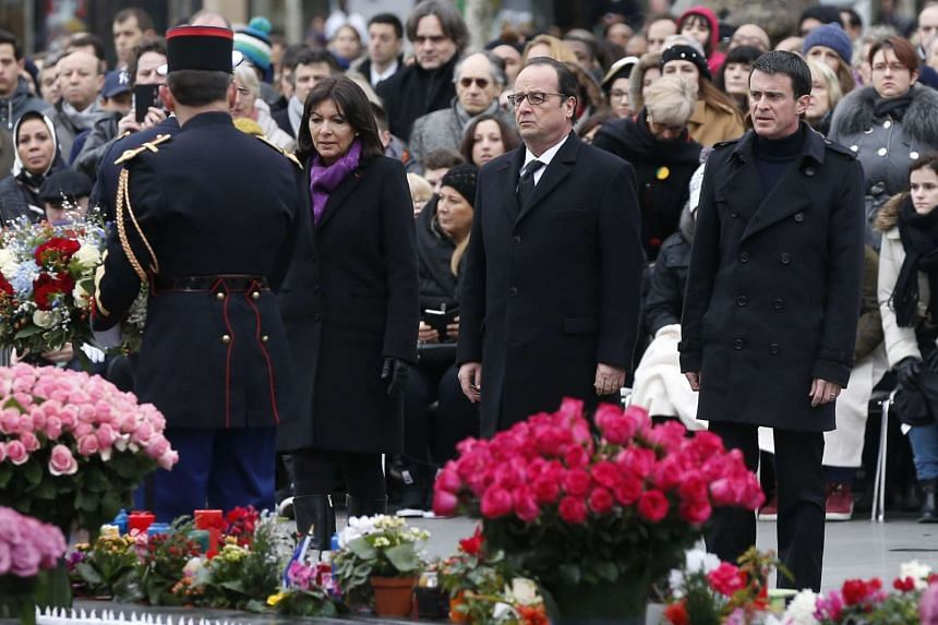 French President Francois Hollande (centre), Paris Mayor Anne Hidalgo (left), and Prime Minister Manuel Valls (right) attend a ceremony to pay tribute to the victims of the 2015 terror attacks.