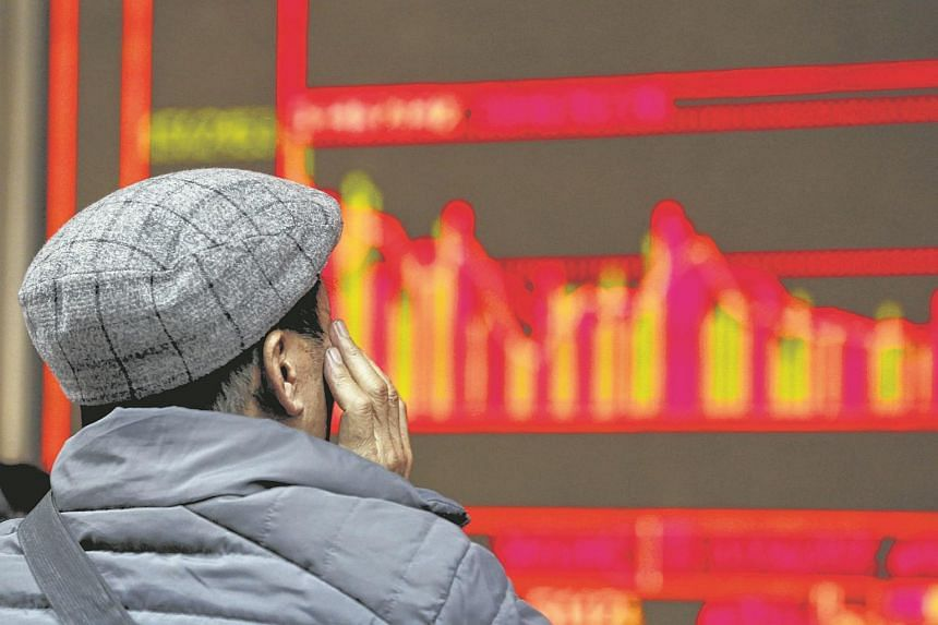 A man looks at an electronic board showing stock information at a brokerage house in Beijing, China on Jan 6.