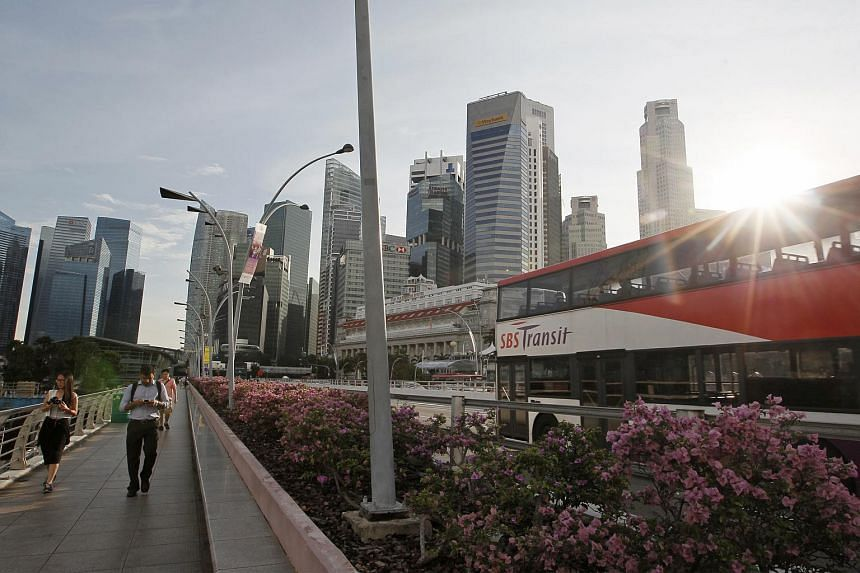 People walk along the Esplanade Bridge, back-dropped by the skyline of the Central Business District (CBD), as an SBS bus passes by on Nov 29, 2013.
